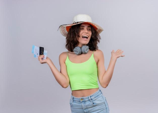 Веселая молодая женщина с короткими волосами в зеленом топе в наушниках в шляпе от солнца держит билеты на самолет и кредитную карту на белом фоне