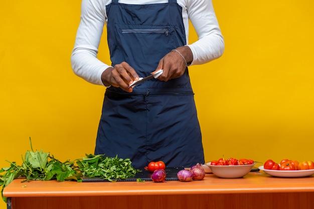 테이블에 토마토, 양파, 야채와 함께 칼을 청소하는 요리사