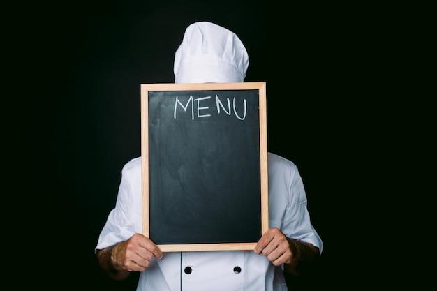 흰색 모자와 재킷을 입은 요리사가 다음과 같은 칠판으로 얼굴을 가립니다. 검정색 배경에 메뉴입니다. 레스토랑, 음식 및 요리 학교 개념입니다.