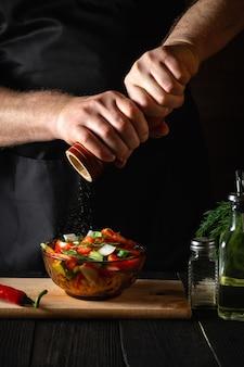 Шеф-повар на кухне ресторана добавляет перец в салат из свежих овощей