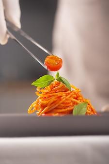 白い制服と手袋をしたシェフが、ピンセットでトマトソースのパスタにチェリートマトを添えます