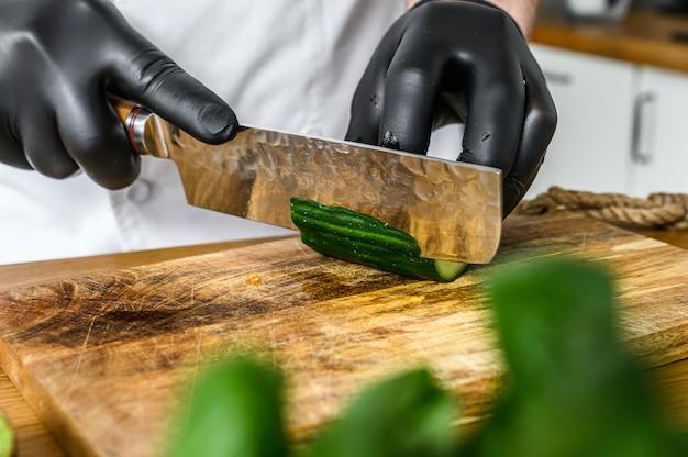 黒い手袋をしたシェフが木製のまな板で新鮮な緑のキュウリをスライスしています。健康的な有機食品の調理の概念