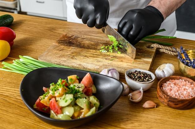 黒い手袋のシェフが木製のまな板で新鮮なねぎをスライスしています。健康的な有機食品の調理の概念