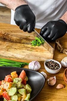 Шеф-повар в черных перчатках нарезает свежий зеленый лук на деревянной разделочной доске.