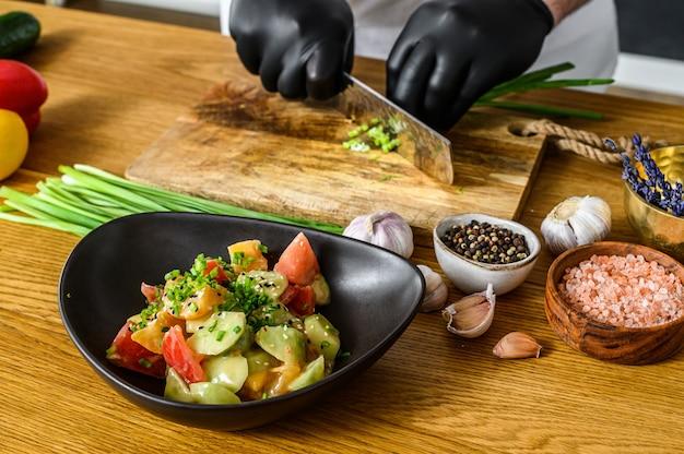 黒い手袋のシェフが木製のまな板で新鮮なねぎをスライスしています。