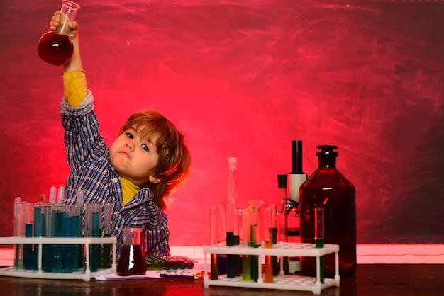 화학 시연. 파란색 벽에 재미 밝은 웃는 어린 소년. 학교