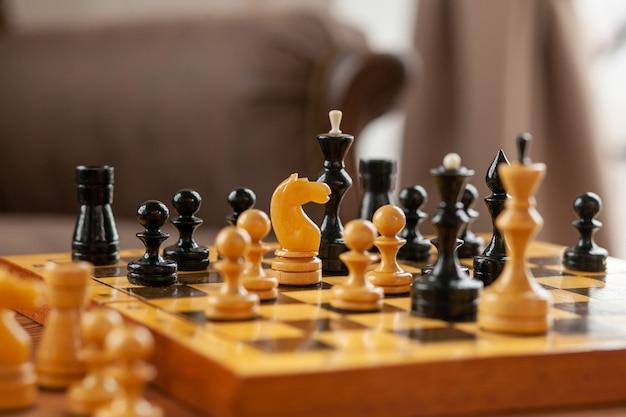 Шахматная фигура - это лошадь, стоящая на шахматной доске. деревянная шахматная доска на винтажном столе, выборочный фокус.