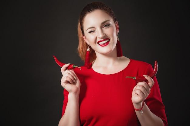 赤いオーバーオールを着たシックな赤髪の若い女性は、手に唐辛子を持っています明るい外観。