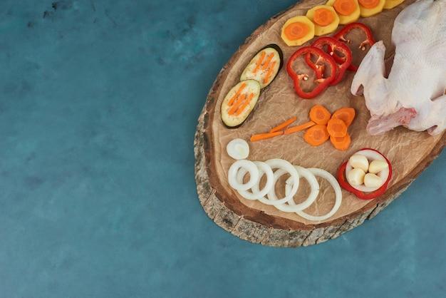 木の板に野菜を乗せた鶏肉。