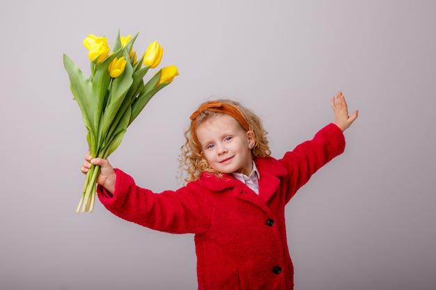 Ребенок блондинка с букетом желтых тюльпанов