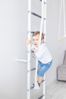 소년이 스웨덴 집 벽에서 운동을하거나 운동을하는 아이