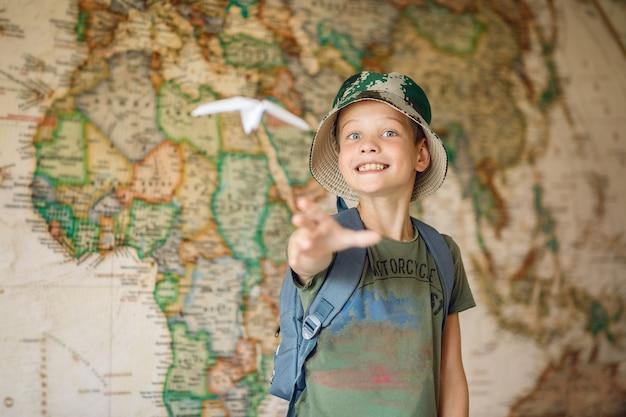 未来の旅行者である子供が紙飛行機を空中に打ち上げる