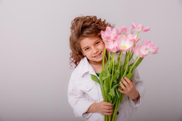 Ребенок девочка держит букет из желтых тюльпанов