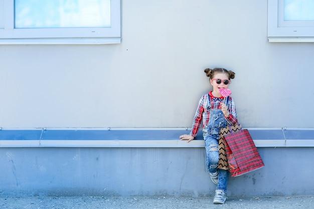 ロリポップを手にした女の子がデニムジャンプスーツとサングラスで路上に座っている子供
