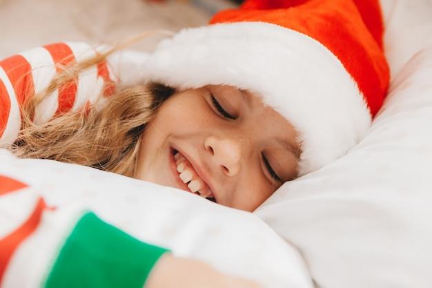 Ребенок, маленькая девочка в рождественской пижаме и шапке деда мороза, спит дома на кровати.