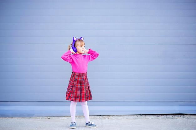 子供、男子生徒は、ワイヤレスの明るいヘッドホンで音楽を聴きます。最新のbluetoothヘッドフォン