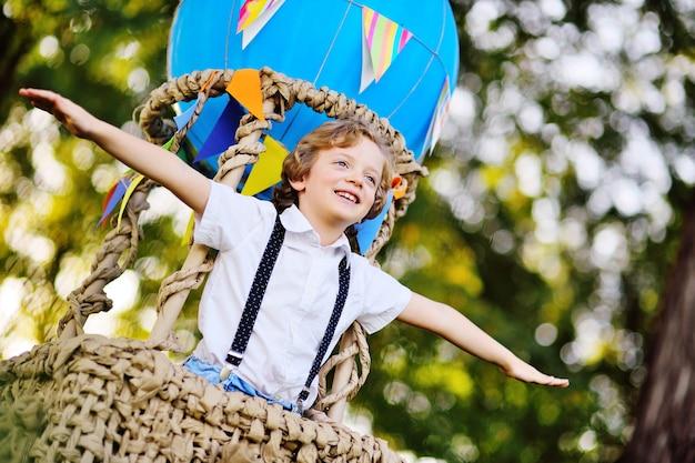 Ребенок маленький мальчик с вьющимися волосами в корзине из синего воздушного шара улыбается и смотрит вдаль на фоне зелени и солнца.