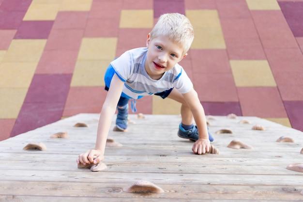어린 소년은 여름에 놀이터에서 등반 벽을 꼭대기로 올라갑니다.