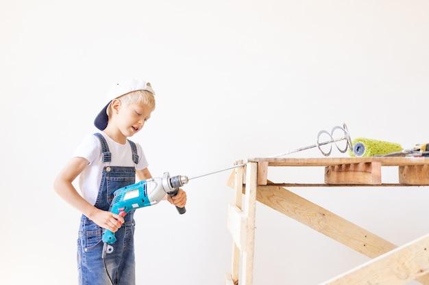 Ребенок-строитель держит миксер у белой стены