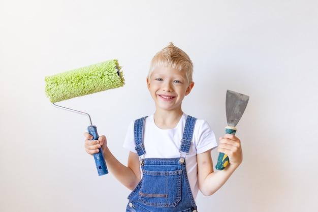 어린이 빌더는 흰 벽이있는 아파트에 건설 도구를 보유하고, 금발 머리를 가진 어린이는 벽, 텍스트를위한 장소, 수리 개념을 페인트합니다.