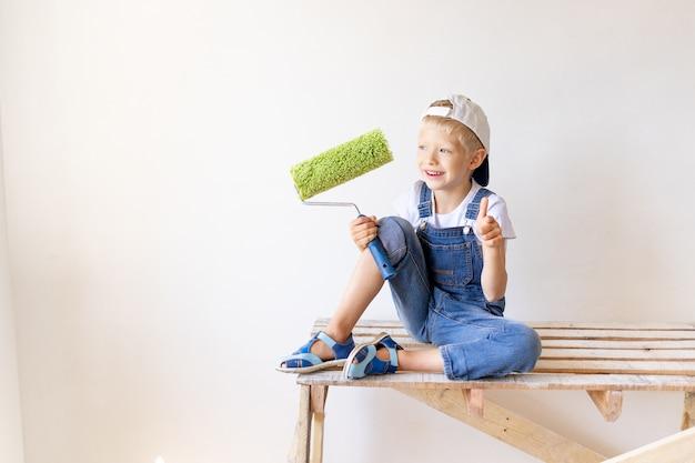 Ребенок-строитель сидит на строительной лестнице с роликом в руках и показывает палец вверх