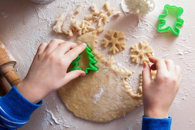Ребенок нарезает печенье в форме елки и снежинки. рождественское праздничное настроение, выпечка, семья, домашняя концепция