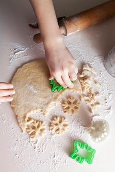 Ребенок нарезает печенье в форме елки и снежинки. рождественское настроение, выпечка, семья, домашняя концепция