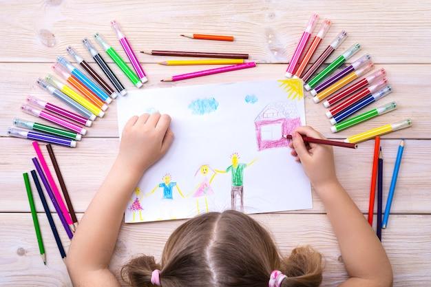 아이는 가족과 함께 생일 카드를 그립니다. 다채로운 펠트 펜과 연필로 아이가 만든 그림. 행복한 가족. 어린이 그림