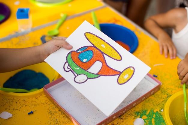子供は色付きの砂の絵で描きます。漫画のキャラクター。