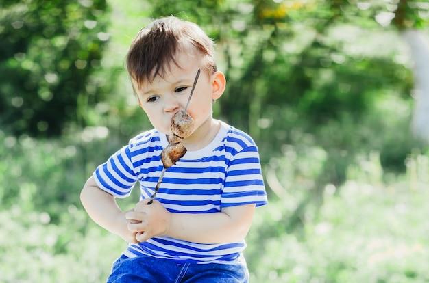 한 아이가 나무와 풀의 공원이나 숲의 자연 녹색 배경에서 꼬치에 케밥을 먹습니다.