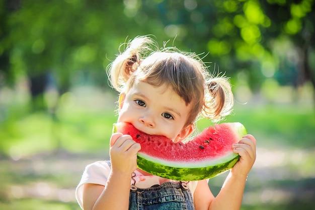 아이는 수박을 먹는다. 선택적 초점.