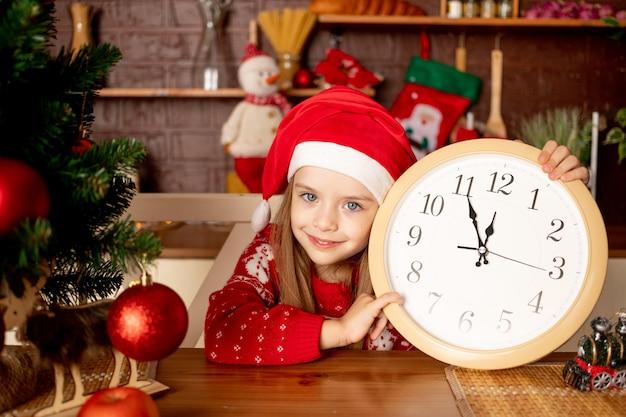 빨간 공이 있는 크리스마스 트리 옆 어두운 부엌에 큰 시계가 있는 산타 모자를 쓴 어린 소녀는 새해와 크리스마스의 개념을 기뻐하고 미소 짓습니다.