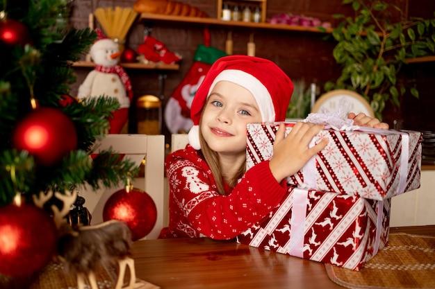 빨간 공이 있는 크리스마스 트리 옆 어두운 부엌에서 선물을 들고 산타 모자를 쓴 어린 소녀, 새해와 크리스마스의 개념