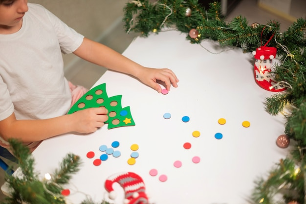 頭に新年の帽子をかぶった白いtシャツを着た子供の女の子が、おもちゃのオリジナルのクリスマスツリーソーターをカットします。クリスマスの伝統の概念。クリスマスにモンテッソーリの細かい運動技能の発達。