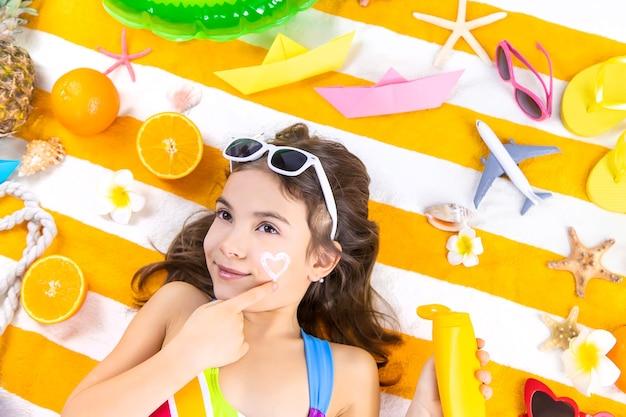 子供の女の子が彼女の肌に日焼け止めを塗ります。セレクティブフォーカス。キッド。