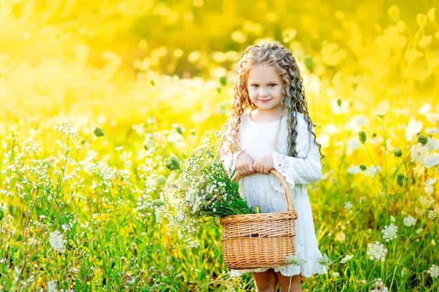 子供の女の子は花のある野原に立って、夏に彼女の手でバスケットを保持しています