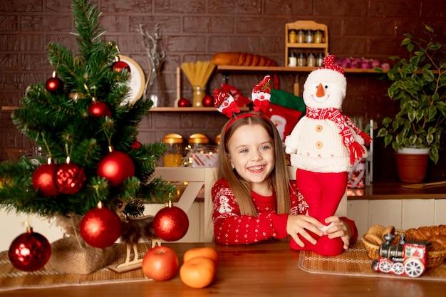 빨간 공이 있는 크리스마스 트리 근처의 어두운 부엌에 눈사람이 있는 어린 소녀, 새해와 크리스마스의 개념