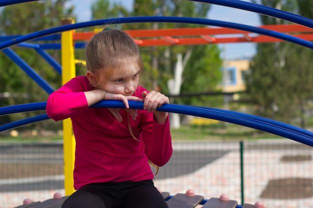 Девочка со светлыми волосами в розовой футболке грустно сидит на детской площадке.