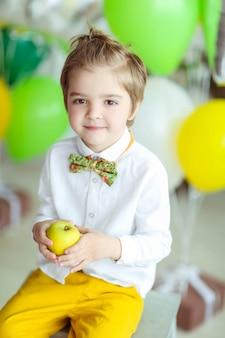 Ребенок веселится и играет с воздушными шариками в комнате, украшенной разноцветными