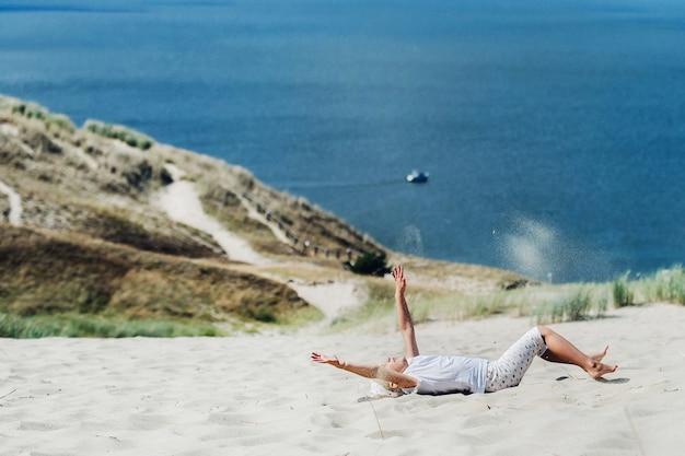 Ребенок развлекается в песчаных дюнах на пляже в ниде, литва.