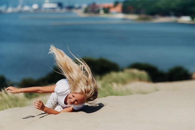 Ребенок веселится в песчаных дюнах на пляже в ниде, литва.