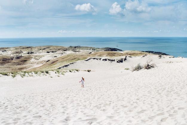 Ребенок развлекается в песчаных дюнах на пляже в ниде.