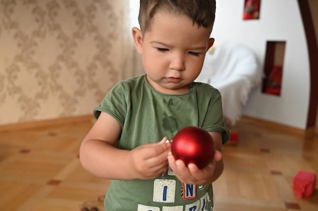 빨간 크리스마스 공을 들고 아이입니다. 고품질 사진