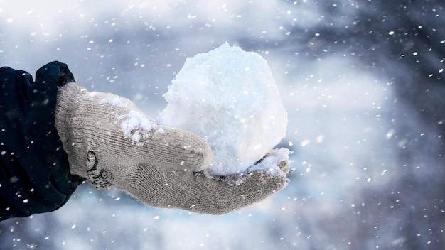 Ребенок держит в руке снежок на улице во время снегопада