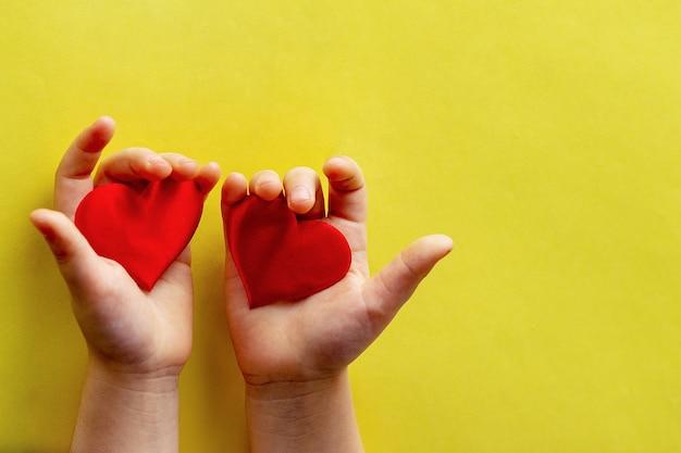 Ребенок держит в ладонях два красных сердца
