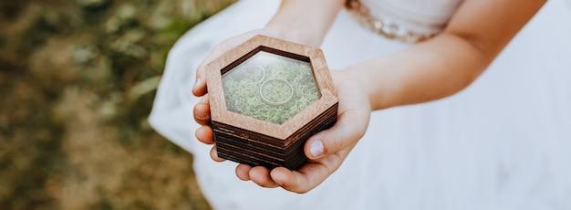 Ребенок держит руками два обручальных кольца в деревянном ящике с растительным мхом