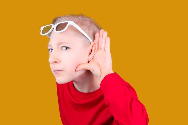3dメガネをかけた子供が手を耳に当て、何かを聞こうとします