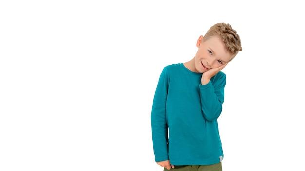 자작나무 재킷을 입은 아이가 미소를 지으며 뺨을 강물처럼 잡고 있습니다. 흰색 격리 된 배경입니다.