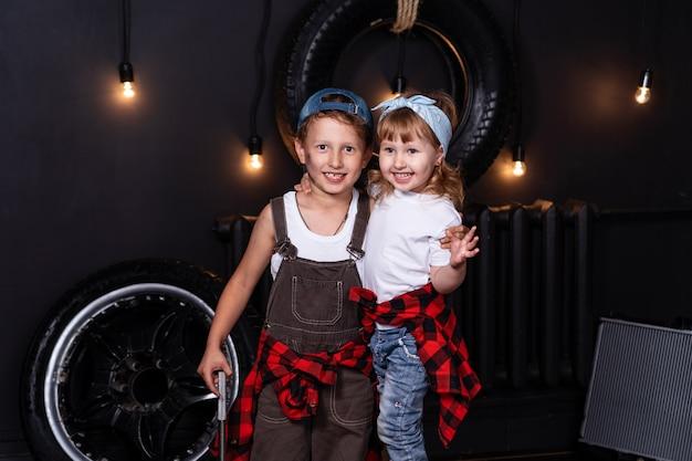 Ребенок в авторемонтной мастерской среди колес и автозапчастей. мальчик обнимает девушку