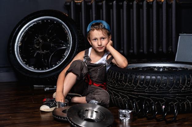 Ребенок в авторемонтной мастерской среди колес и автозапчастей